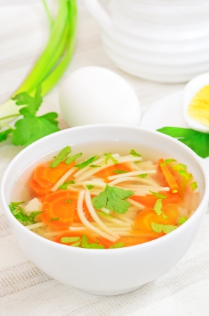 Chicken soup with vegetables in white bowl on a table photo