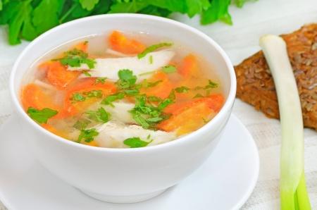 sopa de pollo: Sopa de pollo con verduras en un recipiente blanco sobre una mesa Foto de archivo