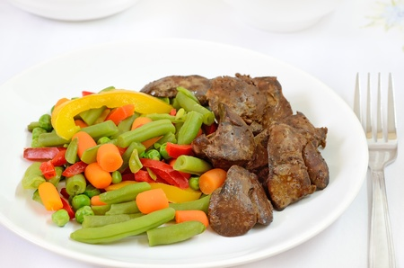 Boiled vegetables with chicken liver on white plate on a table Stock Photo