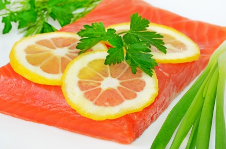 Salted salmon fillet and lemon slices on the white plate photo