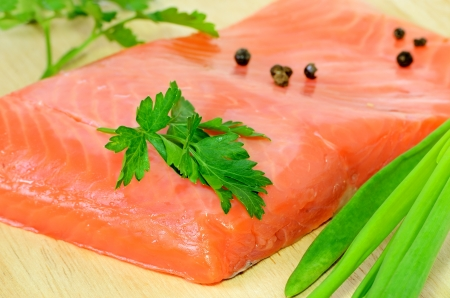 Salted salmon fillet, parsley and green onion on a wooden chopping board photo