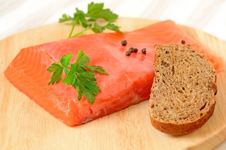 Salted salmon fillet, parsley and slice of bread on a wooden chopping board photo