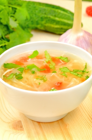 Sauerkraut soup in white bowl on wooden table Stock Photo