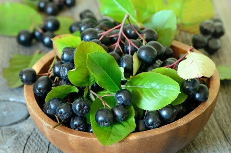 Black chokeberry in brown bowl on wooden table