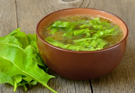 Sorrel soup in brown bowl on the wooden table