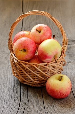 Apples in the wicker basket on a wooden table photo