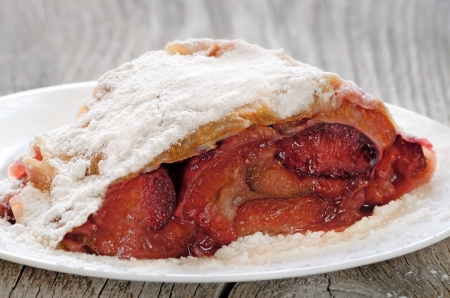 Strudel with plums on a white plate on a wooden table photo