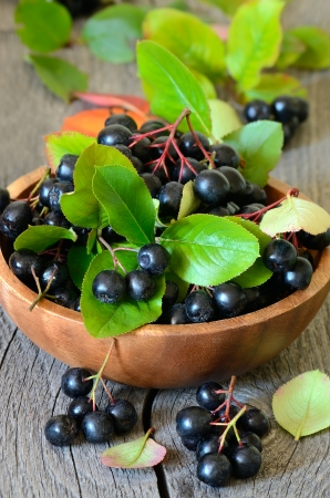 Black chokeberry in brown bowl on wooden table photo