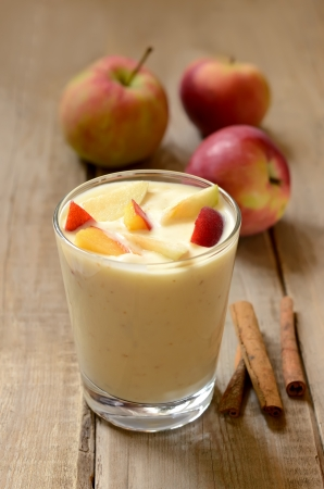 Yogurt with pieces of apple and peach in glass on wooden table