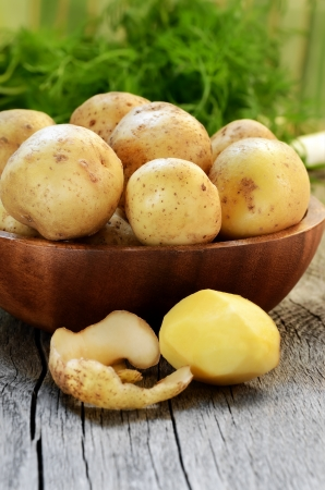 Raw potatoes in bowl on wooden table Stock Photo