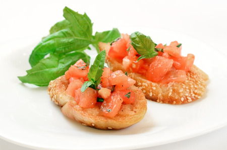Bruschetta with tomato and basil on white plate photo
