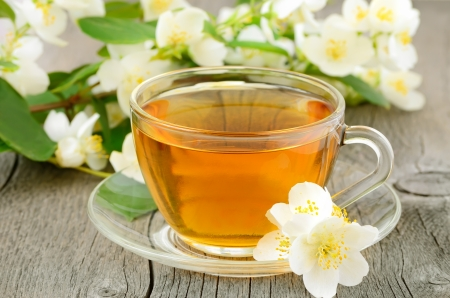 Cup of herbal tea with jasmine flowers on wooden table