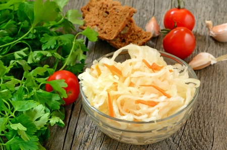 Sauerkraut in glass bowl on wooden table Stock Photo