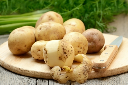Raw potatoes on wooden table Stock Photo