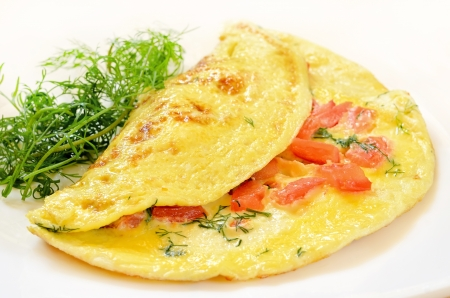 Omelet with tomatoes and herbs on white plate