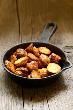 Roasted potato in a frying pan on wooden table Stock Photo