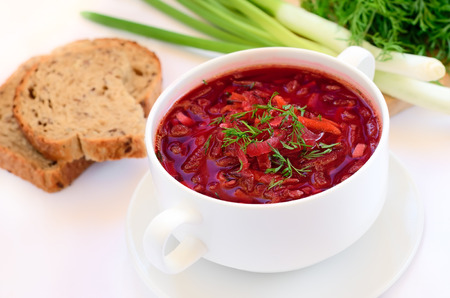 Red borscht  soup with dill in white bowl