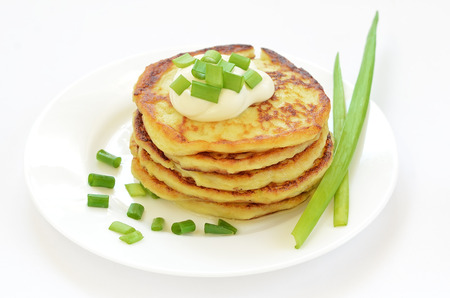 Potato pancakes with green onion on white plate photo