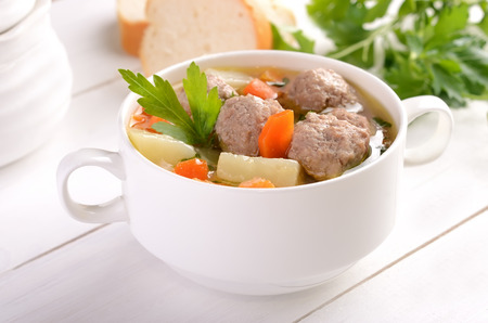 minestrone: Meatball soup in a white bowl on a wooden table Stock Photo