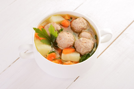 Meatball soup in white bowl on wooden table