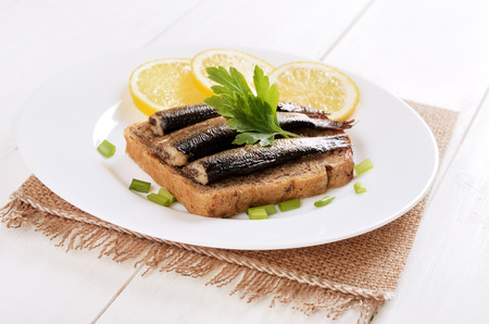 Sprats sandwiches on white plate on wooden table photo