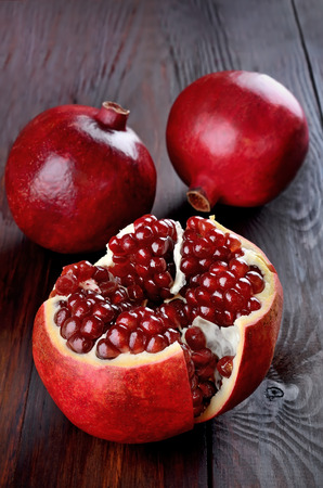 Pomegranate fruits on wooden table photo