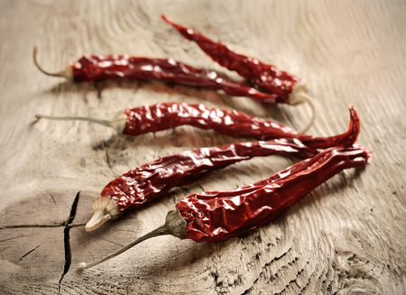 Dry chili pepper on old wooden surface