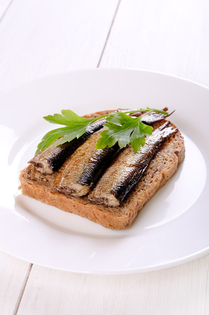 sprats: Sprats sandwiches on white plate on wooden table