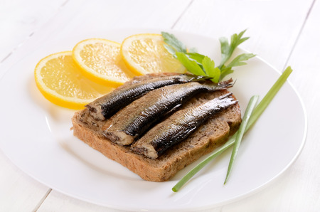 Sprats sandwich on white plate photo