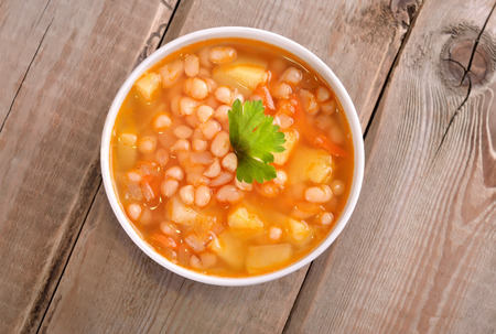 wooden table top view: Bean soup in white bowl on wooden table, top view