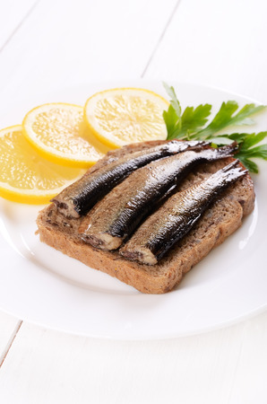 Sprats sandwich and lemon slices on white plate photo