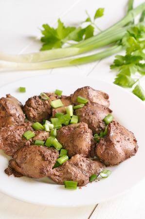 higado de pollo: H�gado de pollo con la cebolla verde en la placa blanca