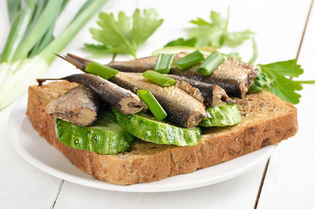 sprats: Sprats sandwich on white plate on wooden table