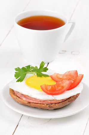 Sandwich with fried egg, tomato slices, salami and tea on wooden table photo