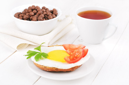 Sandwich with fried egg, cereal chocolate balls and tea cup photo
