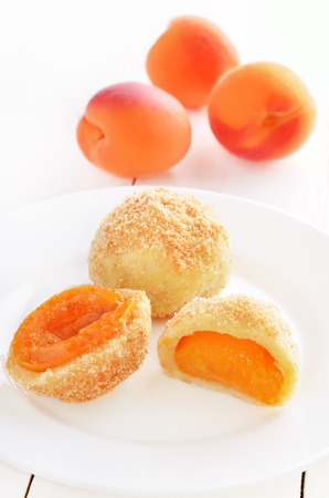 Dumplings with apricots on white plate photo