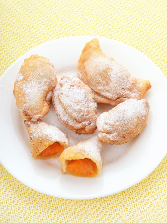 Cakes with fresh apricots on white plate, top view photo