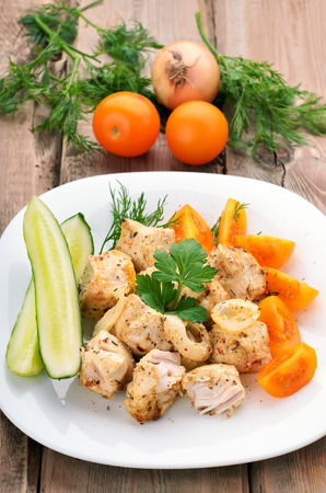 Chicken shish kebab on wooden table photo