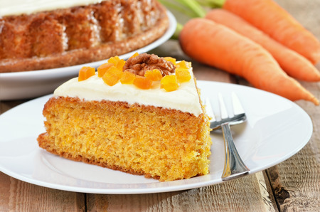Piece of carrot cake with icing decorated dried apricots and walnut on white plate on rustic table