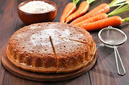 Carrot cake, flour and fresh carrot on wooden table