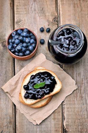 Toasted bread with blueberry jam and jam in glass jar on wooden table, top view photo