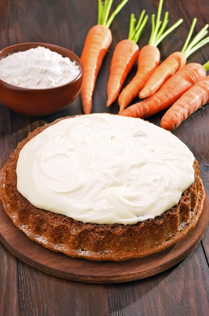 Carrot pie with icing and fresh carrot on wooden table photo