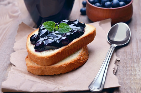 Toasted bread with blueberry jam on wooden table