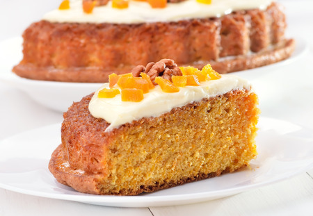 Piece of carrot pie with icing decorated dried apricots and walnut on white plate photo