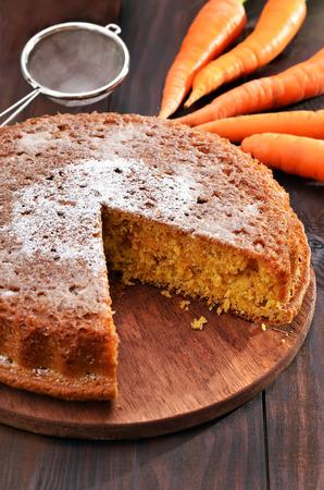 Wortel taart en verse wortel op houten tafel