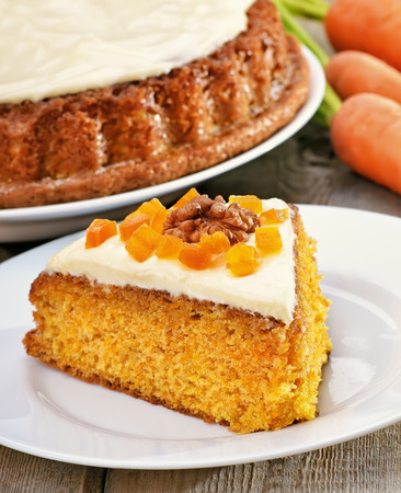 Piece of carrot cake with icing decorated dried apricots and walnut on white plate photo