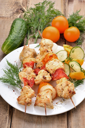 Chicken shish kebab and fresh vegetables on wooden table photo