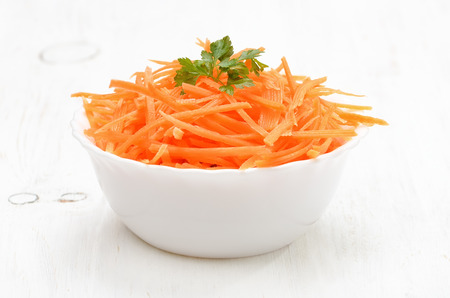 Grated carrot in bowl on white wooden table