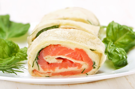 Salmon lavash rolls with cheese and herbs, close up view photo