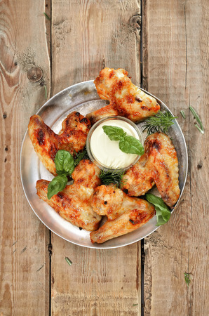 chicken wings: Fried chicken wings with sauce on rustic table, top view